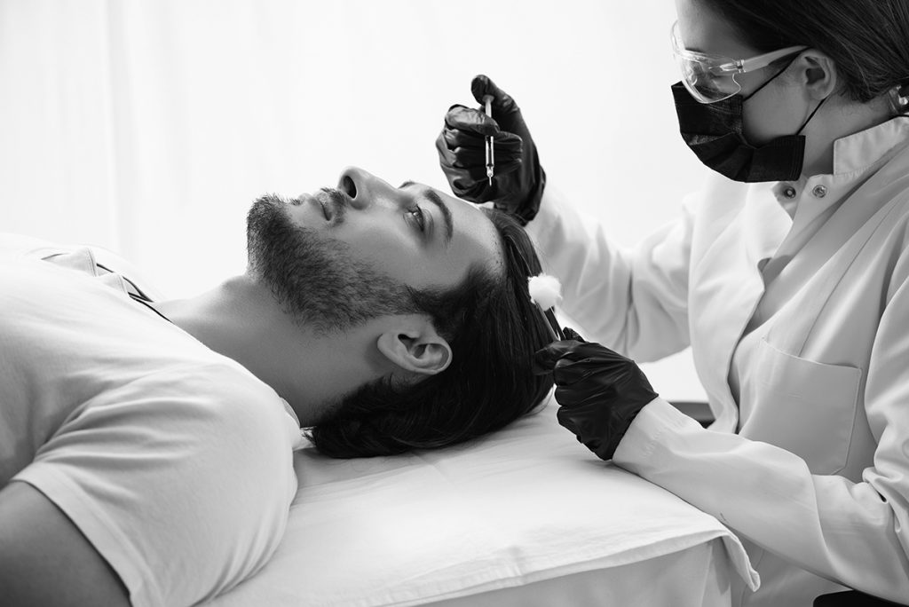This is an image of a doctor and a man getting Hair Restoration Nashville